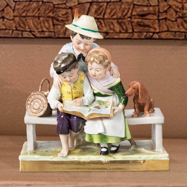 """Porzellan-Figurengruppe """"Das Bilderbuch"""" aus glasiertem Porzellan, farbig dekoriert"""