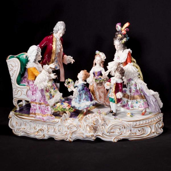 """Figurengruppe mit Rüschenbelag """"Großmutters Geburtstag"""" aus glasiertem Porzellan, farbig dekoriert"""